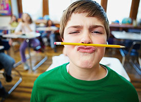 Image of a little boy with a pencil clenched between his nose and mouth.