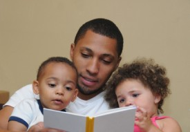 An image of an adult man reading to a little boy and a little girl