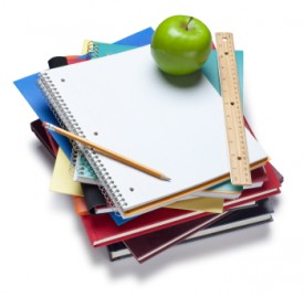 An image of a stack of textbooks with a ruler, pencil and apple sitting on top.