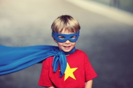 An image of a little boy in a superhero mask and a cape.