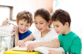 An image of three kids reading together.