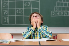 An image of a child in a classroom, sitting at a desk, with his head in his hands.