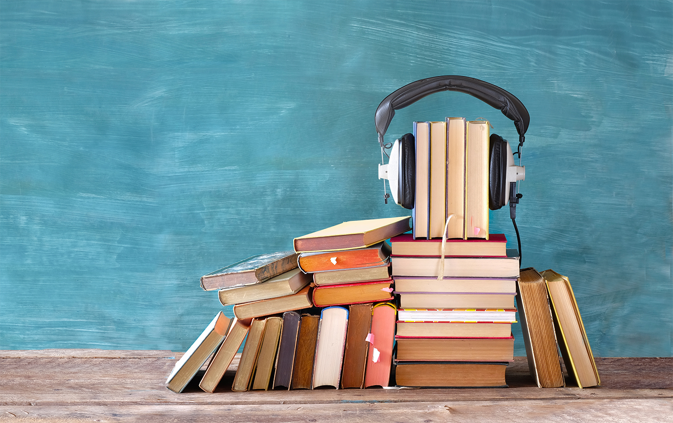 auditory processing and reading represented by a stack of books with headphones