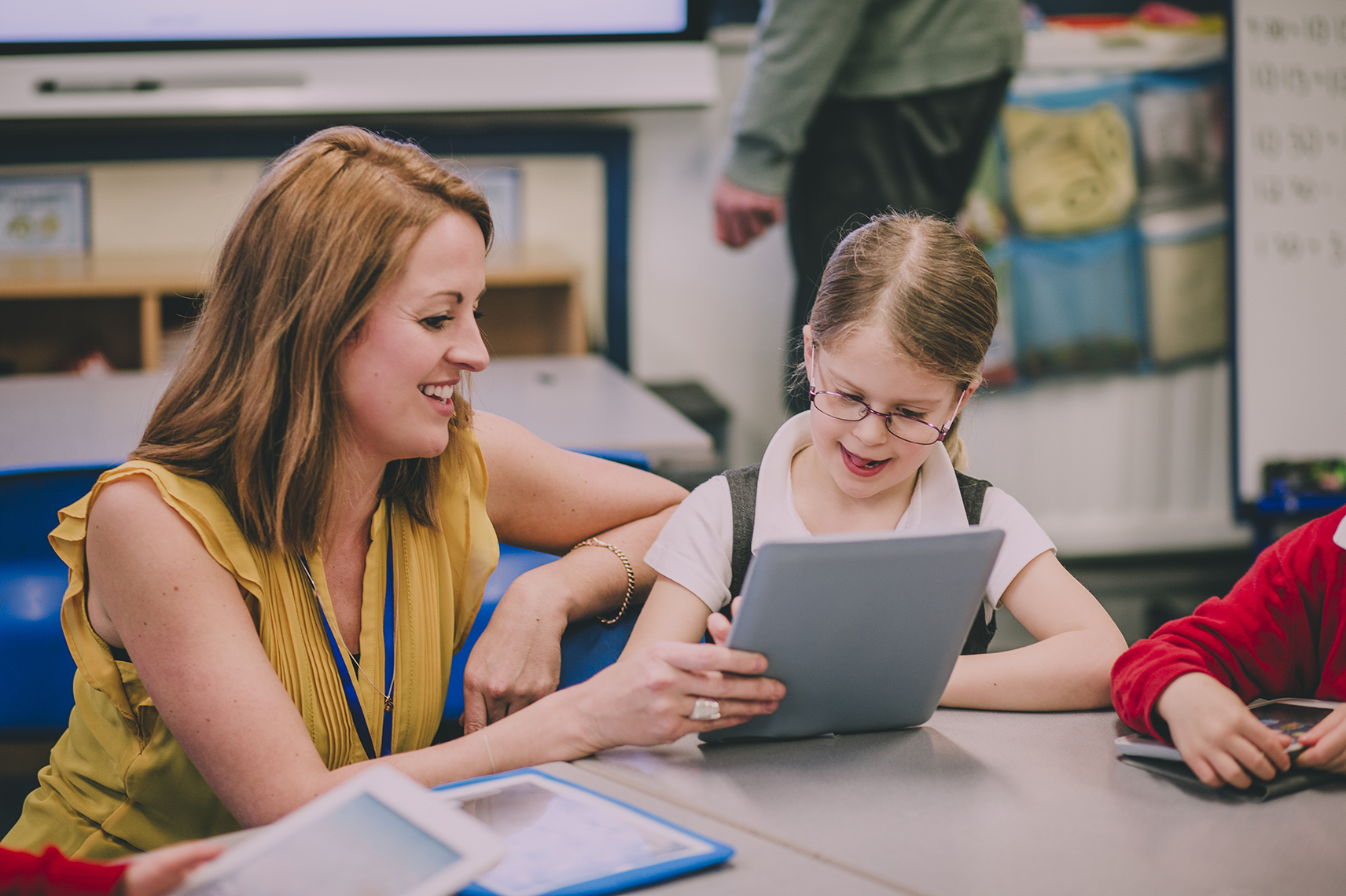Teacher trust Fast ForWord; a teacher working with an elementary student on a tablet at a classroom table